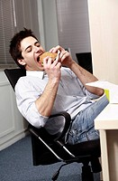 Office worker eating hamburger at desk