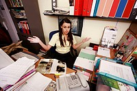 Female office worker at cluttered desk