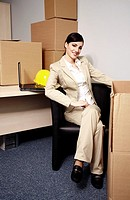 Businesswoman with laptop among boxes (thumbnail)
