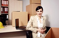 Businesswoman with laptop among boxes