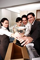 Four business people holding trophy in office