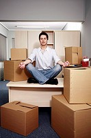 Businessman on desk among boxes meditating