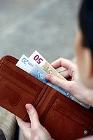 Closeup of hands holding wallet with euros