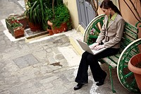 Businesswoman with laptop on a bench