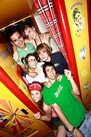 Teenagers at photo booth in arcade (thumbnail)