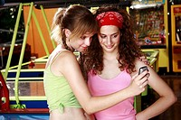 Female teenagers taking picture of themselves with cell phone camera (thumbnail)