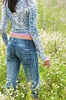 detail of young woman walking through summer meadow