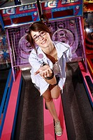 Female teenager on amusement park game with hand out (thumbnail)