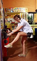 Female teenager playing game in amusement park arcade (thumbnail)