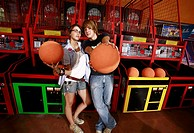 Teenage couple at game in arcade (thumbnail)