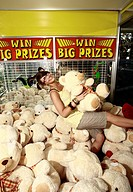 Female teenager among teddy bears in arcade