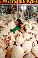 Teenage couple among teddy bears in arcade