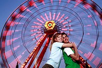Teenage couple at Ferris wheel in amusement park