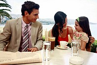 Couple with daughter at seaside cafe table (thumbnail)