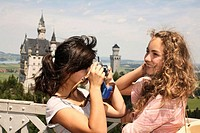 teenage girl taking picture of friend in front of Neuschwanstein castle in Bavaria