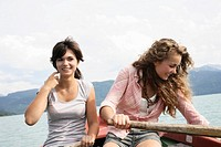 portrait of two teenage girls sitting in rowing boat on Bavarian lake