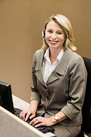 Businesswoman on computer and phone