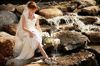 Bride dipping her toe in a stream