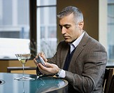 Middle Eastern man using electronic organizer at bar