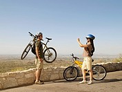 Hispanic woman taking photograph of boyfriend with bicycle