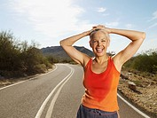 Senior Hispanic woman taking break from jogging (thumbnail)