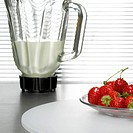 Strawberries on plate in front of mixer, close-up
