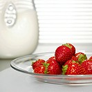 Strawberries on glass plate in front of milk jar, close-up