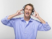 Young man with eyes closed listening to music