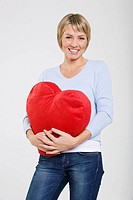 Young woman holding heart-shaped cushion, smiling,portrait