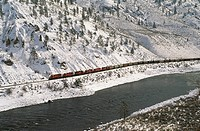 CP Rail train travels under snow covered cliffs in the Thompson River canyon. British Columbia, Canada