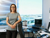 Hispanic businesswoman leaning on chair (thumbnail)
