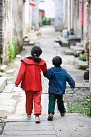 Girl walking with her brother in an alley, Cheng Kan, China
