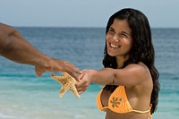 Hispanic woman handing starfish to boyfriend