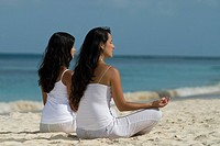 Hispanic women meditating at beach