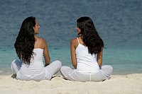 Hispanic women sitting on beach