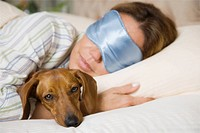 Hispanic woman sleeping with dog