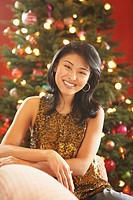 Asian woman in front of Christmas tree