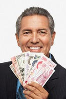 Hispanic businessman holding assorted world currencies