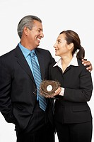 Hispanic professional couple holding nest with dollar sign egg