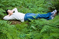 Asian man laying in woods