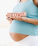 Pregnant African American woman holding &#8220;GIRL&#8221; blocks