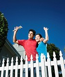 Multi-ethnic couple waving next to fence