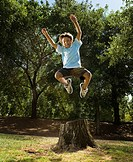 Hispanic boy jumping off tree stump