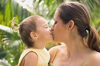 Hispanic mother kissing baby