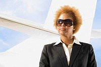 African American businesswoman in front of airplane