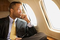 African American businessman on airplane (thumbnail)