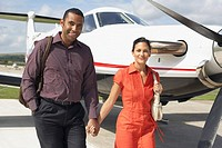 Multi-ethnic couple walking next to airplane