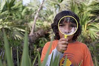 Hispanic boy looking through magnifying glass