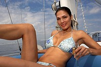 Hispanic woman with champagne on sailboat
