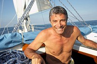 Bare-chested man on sailboat